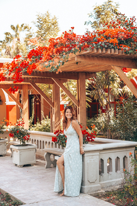Ashley standing in the garden under some blooming bougainvilleas