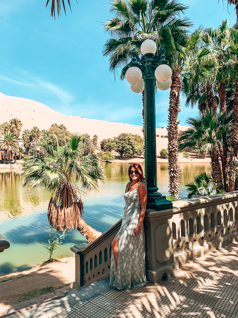 Ashley standing in front of the Huacachina Oasis. Blue green waters surrounded by desert dunes.