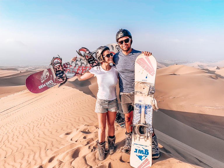 Ashley and Chris standing at the top of a dune getting ready to do some Sandboarding